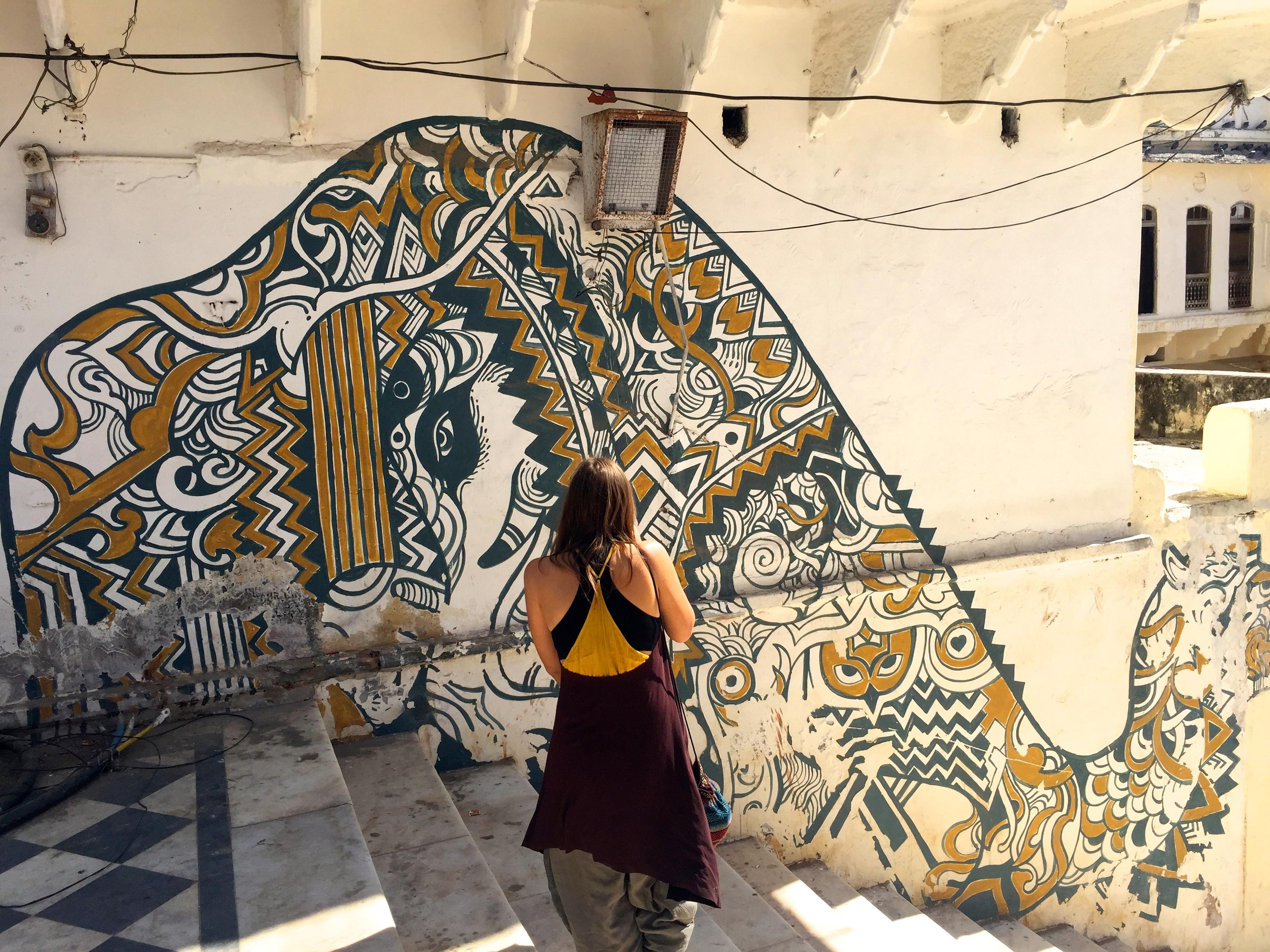Frau vor einem Graffito in Pushkar am heiligen See