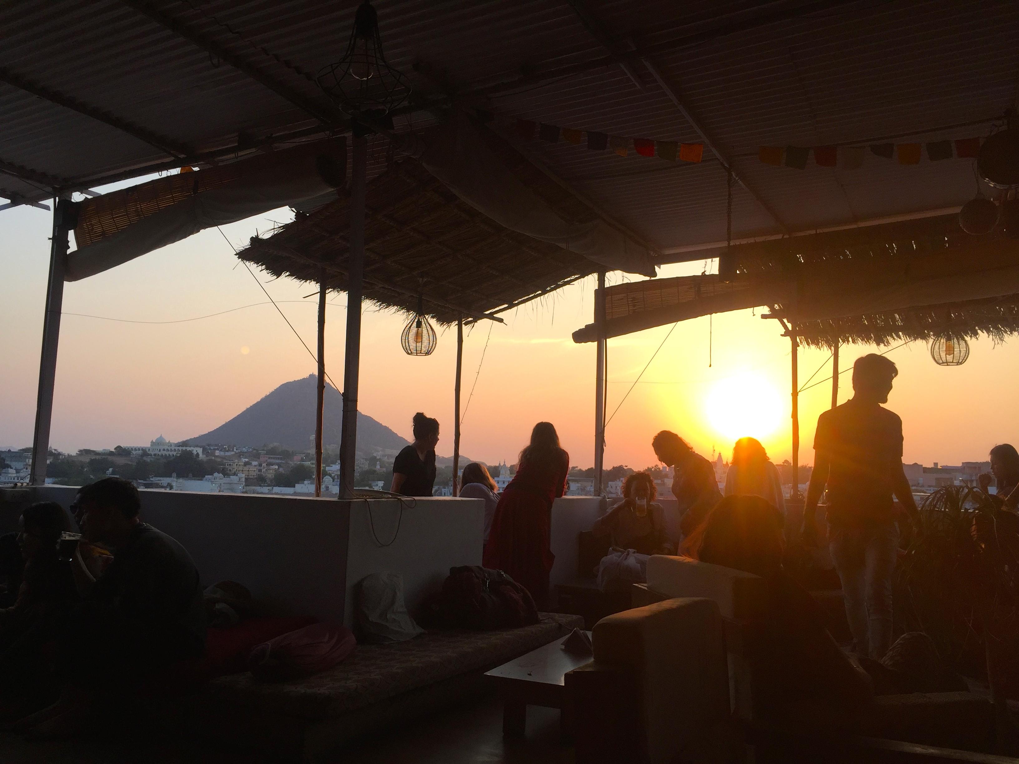 Menschen blicken von einer Dachterasse auf den Pushkar-See