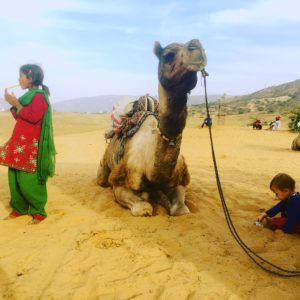 Kind spielt im Sand, daneben entspannt ein Kamel