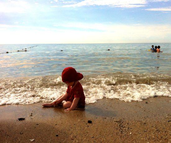 Kleinkinder sollten am Strand immer eine Mütze tragen - auch wenn es schattig wirkt. Sonst droht ein Hitzeschlag.